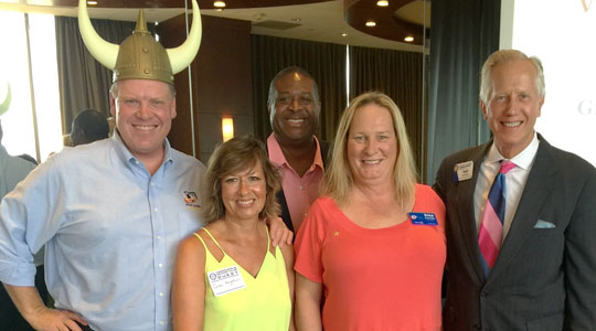 Rotary of Minneapolis August 10 Event - Member with Viking Hat Stands with Group Smiling